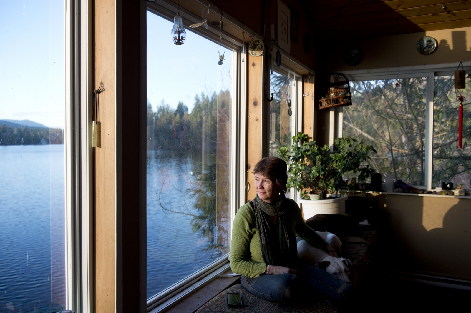"Shelagh Bell Irving looks at Shawnigan Lake from her home on Dec. 11, 2015. Bell Irving was one of the first recipients of an injunction preventing protestors from blockading trucks headed for the SIRM site. ""My grandmother told me from the time I was a little girl that I was here to protect the water,"" said Bell Irving, whose family has owned property on the lake since 1941. ""I can't stop [protesting]. There's been many times I've been so tired from talking about this... I just want this to be done but I can't stop until this is done."""