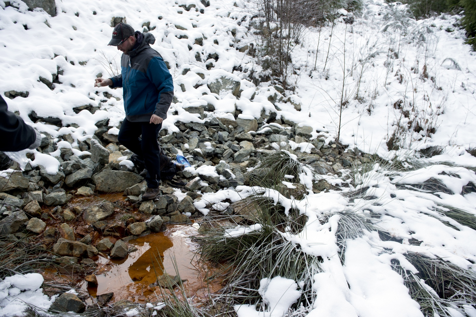 Luke Cross, of Duncan, collects water near Lot 21 on Jan. 1, 2016. Cross is a vocal opponent of the site and posts regular videos on social media to spread awareness. Lot 21, which is adjacent to the South Island Resource Management site Lot 23, is owned by Cobble Hill Holdings. In Oct. 2010, over 1000 tonnes of contaminated soil was dumped in Lot 21 without a permit. The leachate from Lot 21 flows directly in Shawnigan Creek, which later flows into Shawnigan Lake. Lot 21 has been a point of contention between SIRM and the residents of Shawnigan Lake. Todd Mizuik, co-owner of SIRM, maintains the site is dormant. He has also criticized protestors for using leachate from Lot 21 as a key message, claiming the water's colour is solely caused by naturally-occuring iron bacteria. Residents, on the other hand, cite studies showing high levels of thorium, lead and other heavy metals in the leachate from Lot 21.