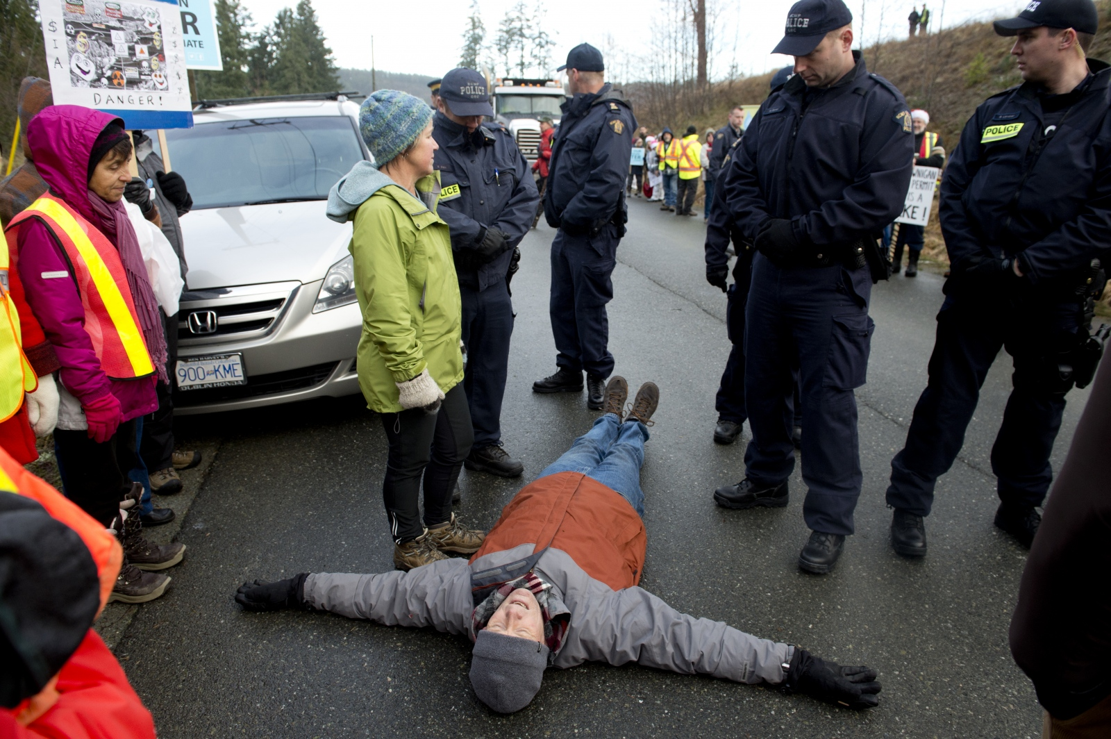 Bruce Stevens, of Shawnigan Lake, lies on the ground to impede dump trucks headed for the South Island Resource Management site on Dec. 22, 2015. Residents gathered en masse on Dec. 22 to block trucks for two hours, resulting in nine arrests.
