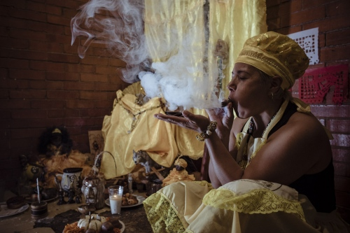 "Liliana in her house in Mexico City. She's a medium and healer, she works with natural elements, prayers and going into a trance to find out the answers from their spirit helpers. She's asking the future the her ""Chamalongos"", in the past they were ancient bones, now the Chamalongos are made by coconut wood"
