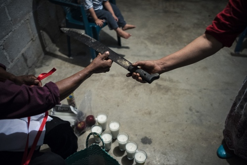"""The healer has been called to heal this 3 years old baby as he was sick very soon. """"He has the gift, the healer said, """"and we need to protect himself from the bad spirits"""". The ritual lasted a couple of hours and has been made with candles, fruits, and egg and ancient prayers. Sierra Negra, Mexico"""