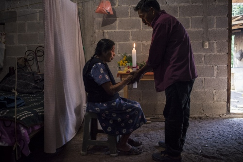 """The curanderos Mario Cubas is protecting a woman house supposely invaded by spirits. The curandero is the only person who has the skills and ability to fight off mal de ojo (the evil eye), or even to put curses on someone: """"as exists good and bad in the world, somebody works in white magic and somebody else in black one"""", said Mario. Tlacotepec, Sierra Negra, Puebla."""