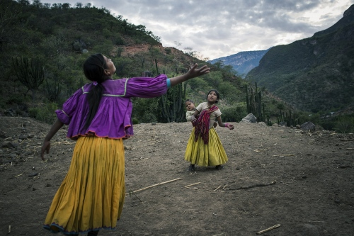 Raramuri sisters with their little brother playing volleyball in front of their house, a sheet metal roof supported by four sticks. The small village is called Munerachi, in Chihuahua.