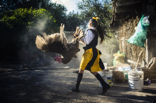 Belen in her backyard is playing with a turkey after school. Animals for own consumption are the first means of subsistence for many families in the rural Mexico. Somentimes they are sacrified as offering.