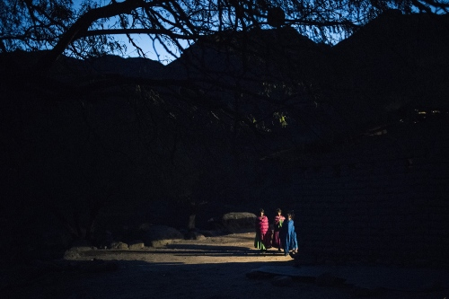 Three sisters in front of their house at the dawn during the Virgen of Guadalupe night. Munerachi village, baja Tarahumara, Chihuahua.