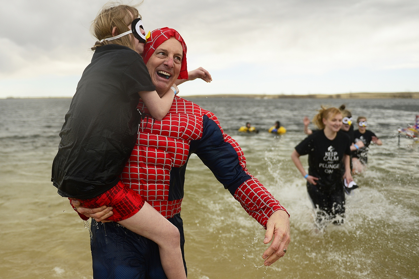2016 Polar Plunge Raises Money and Awareness For Special Olympics Bill McIntosh holds Hannah Hall, 16, after taking the plunge during the 2016 Polar Plunge at the Aurora Reservoir on February 20, 2016 in Aurora, Colorado. Hundreds of people showed up for the annual event dressed in costumes, looking forward to take a dip in the 36 degrees reservoir to support Special Olympics Colorado. (Photo by Brent Lewis/The Denver Post)
