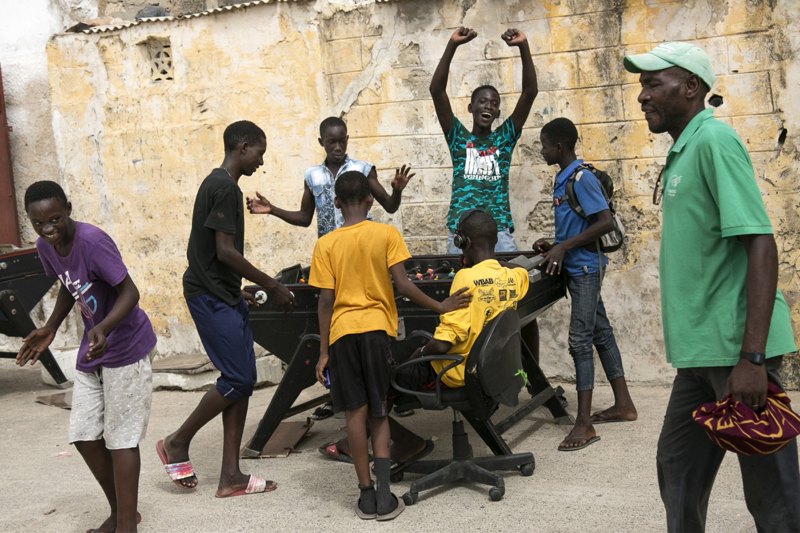 A group of young men celebrate after a game of foosball in St. Louis, Senegal.