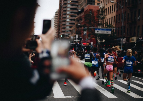 Spectators hurriedly photograph as the lead group of women pass through the Upper East Side during the 2017 New York City marathon. Running through all five boroughs, the New York City Marathon is the largest in the world with 50,766 finishers and nearly 100,000 applicants this year. November 5, 2017.