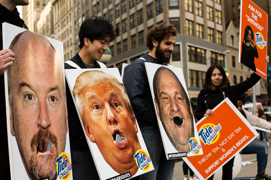 A few students at NYU bring the Tide Pod Challenge featuring Louis C.K., President Trump, and Harvey Weinstein to the 2018 Women's March in New York City. January 21, 2017.