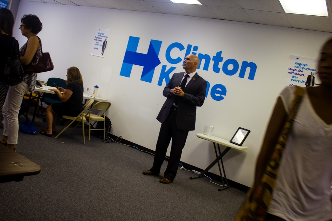 A Secret Service member watches over Anne Holton, wife of Democratic vice presidential candidate Tim Kaine, as she speaks with volunteers at the Democratic coordination campaign office in Richmond, Virginia. August 21, 2016.