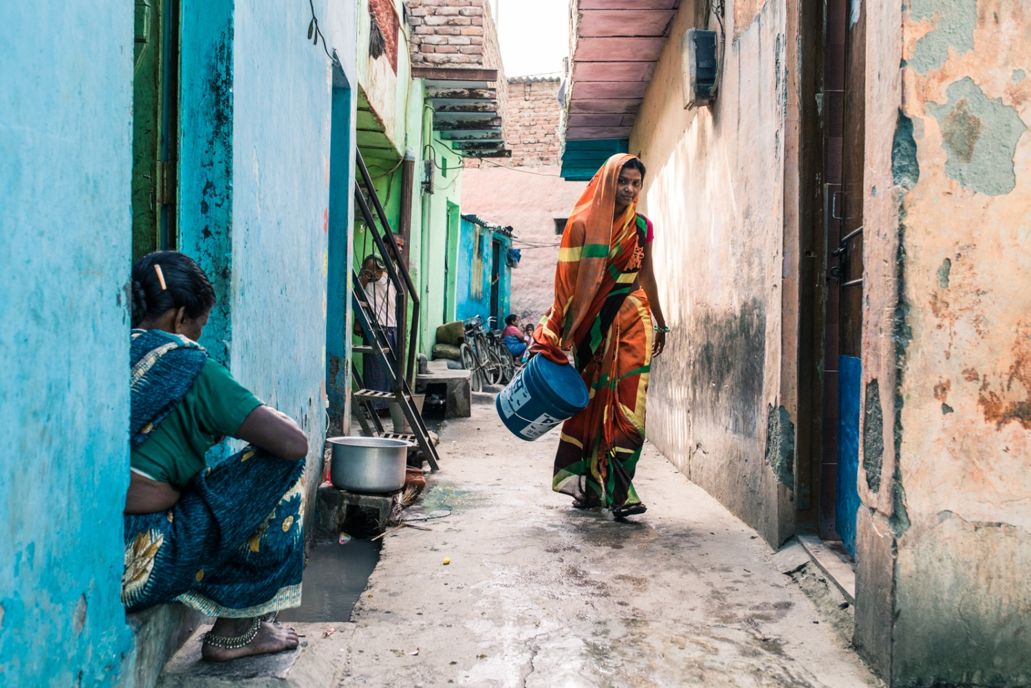 Woman going to collect water in a slum settlement outside New Delhi, India. Climate change is causing rainfall patterns to shift to more extreme variations. Long dry spells in already water starved areas are set to increase putting pressure on cities located in dry locations such as New Delhi.