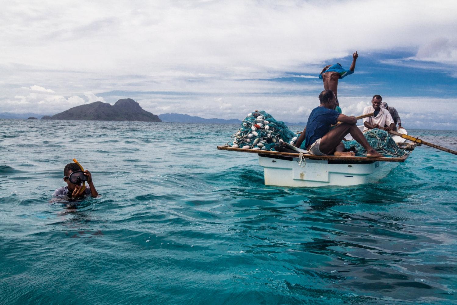 Fijian fisherman on Fiji's Great Sea Reef begin to get ready to dive under to catch their source of income and livlihood, fish. As climate change warms the globe, the ocean's temperature rises with it. Coral reefs that sustain fishing communities, like those that these fishermen are from, are dying out due to warming ocean temperatures. Coral reefs are extremely sensitive to temperature variations.
