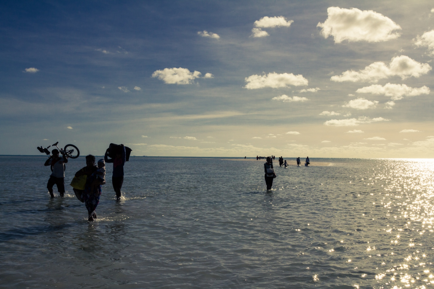 Inter-island migrants walk across the ocean to reach their destination of South Tarawa, Kiribati. As more of the outer and remote islands in Kiribati face climate change impacts, mainly sea level rise, many are moving to the island of South Tarawa, the crowded capital.
