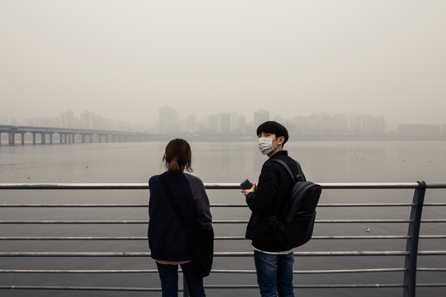 A couple in Seoul, South Korea under a thick blanket of air pollution that covered the city during a spring day. Air pollutants are mostly sourced from fossil fuel burning vehicles and power plants. As air pollutants are released from the burning of fossil fuels, it is realesed in concert with carbon dioxide, the main precusor to climate change.