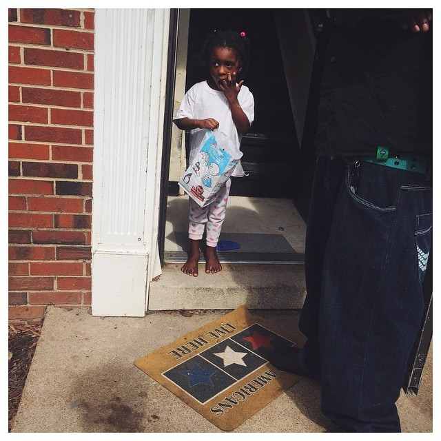 While Joshua breaks the bad news to the family about being unable to move their recently purchased sofa into the apartment, a young girl appears in the doorway and watches the talk as if she has an invested emotional stake in this issue already.