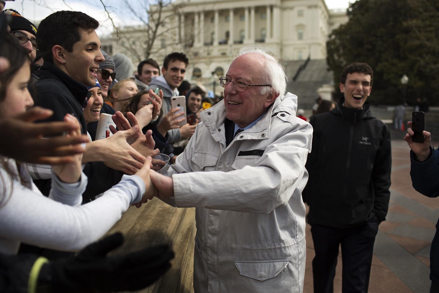 Senator Bernie Sanders shakes hands with students.