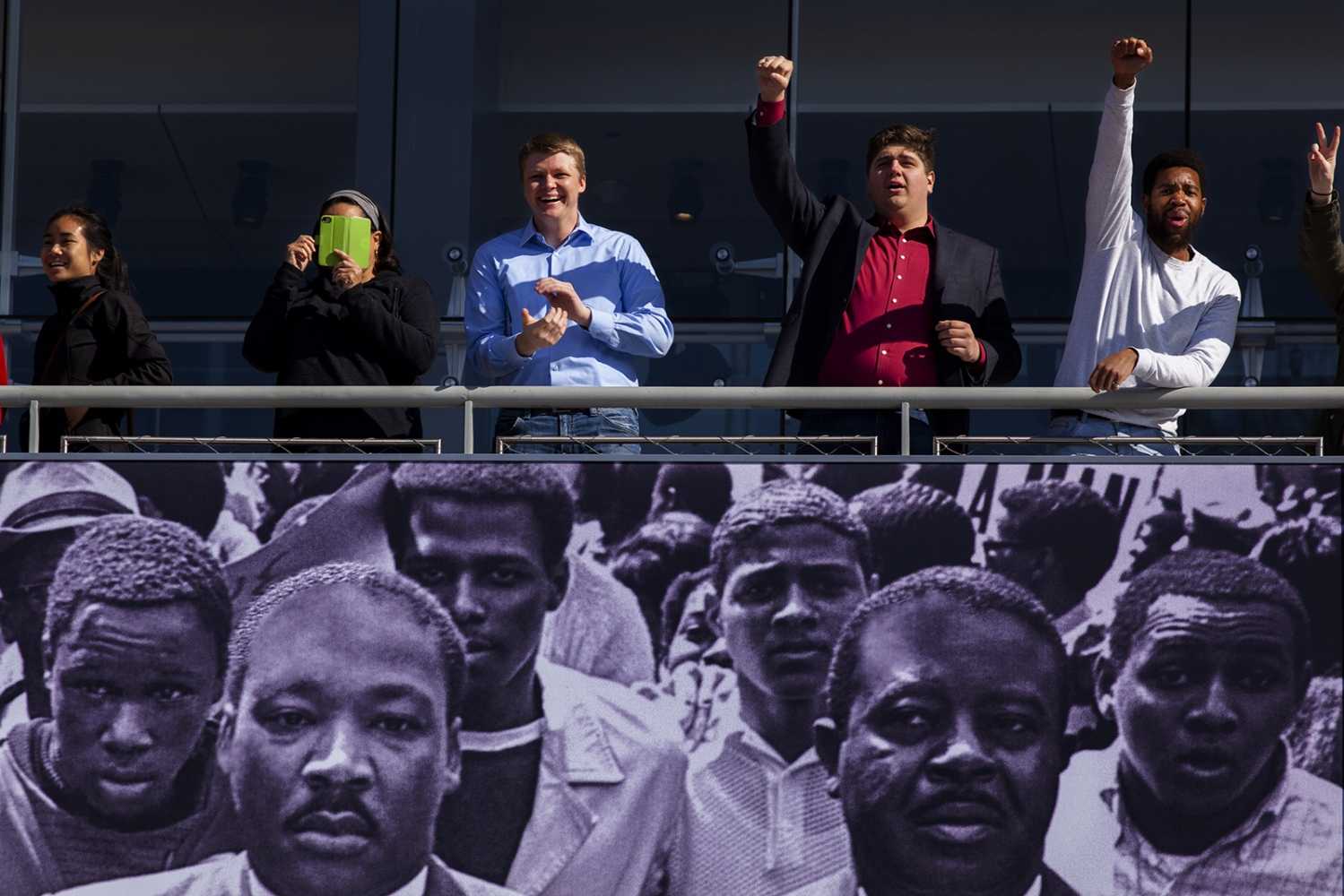 People at the Newseum show their support as the students march down Pennsylvania Avenue to the U.S. Capitol.
