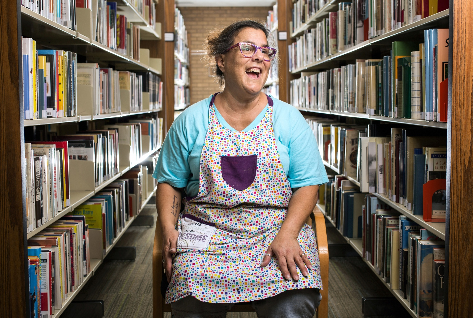 "Laura Comito: ""I got my first library card when I was 4. I learned how to write my name just so I could get a library card. That was it. I've never not had a library card. When I do programming with kids, I come in and I physically get books that tie into whatever classes I'm teaching. Today I picked up books for art around the world, because we're going to Ghana, Africa, Japan, Mexico and Russia. So I spend quite a bit of time crawling around on the floor and looking for books."""