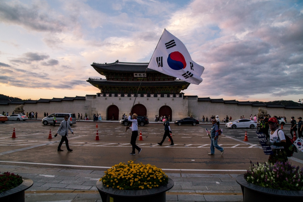 A man waves South Korean flag in front of Gyounbukgung palace. Seoul, South Korea.