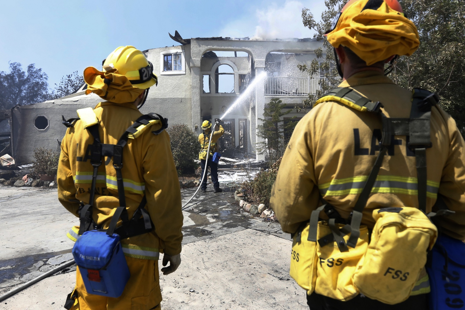 Los Angeles City firefighters use foam to put out hot spots on a damaged house on Iron Canyon Road off of Sand Canyon Road after the Sand Fire swept through on Saturday. Katharine Lotze/The Signal