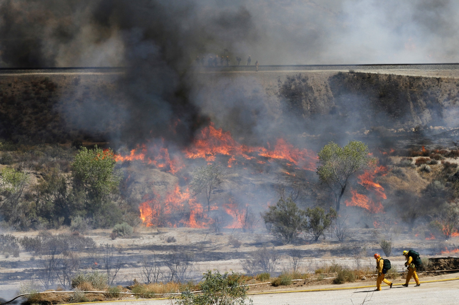 Two firefighters walk down a dirt road into the Santa Clara Riverbed near the Sand Canyon Road exit on Highway 14, toward the Sand Fire shortly after it began on Friday, July 22, 2016. Katharine Lotze/The Signal