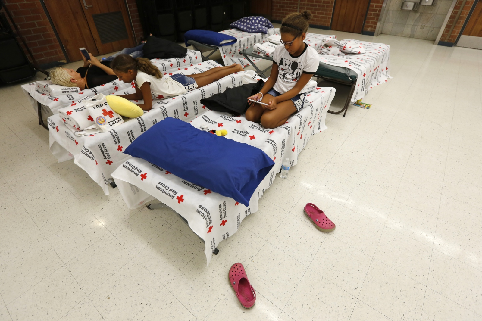 The Kellum family rests in the Hart High School cafeteria after the evacuation center was moved from the gym to the cafeteria to provide air conditioning on Sunday, July 24, 2016. Katharine Lotze/The Signal