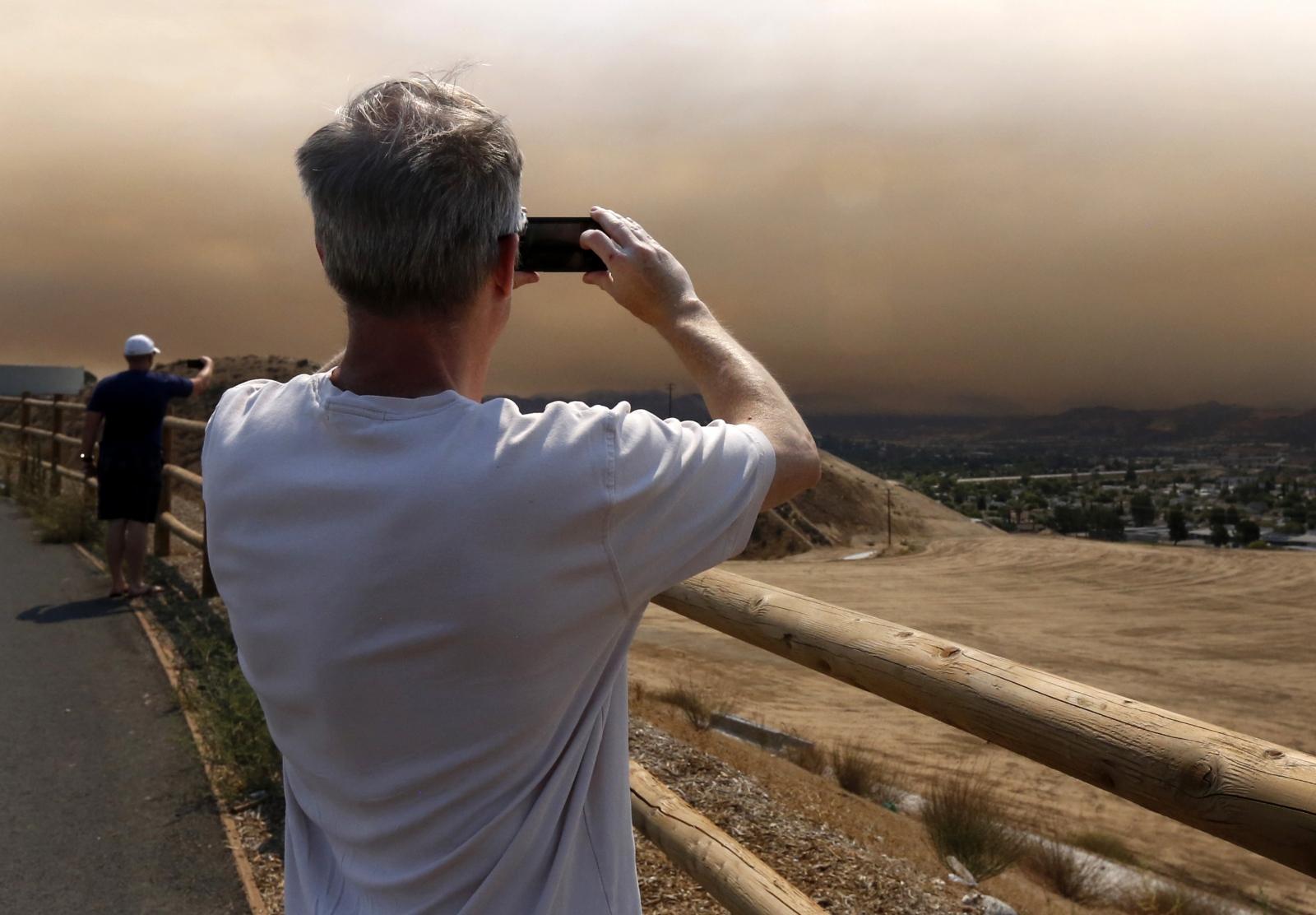 Santa Clarita residents take photos of the smoke as the Sand Fire burns on Saturday, July 23, 2016. Katharine Lotze/The Signal