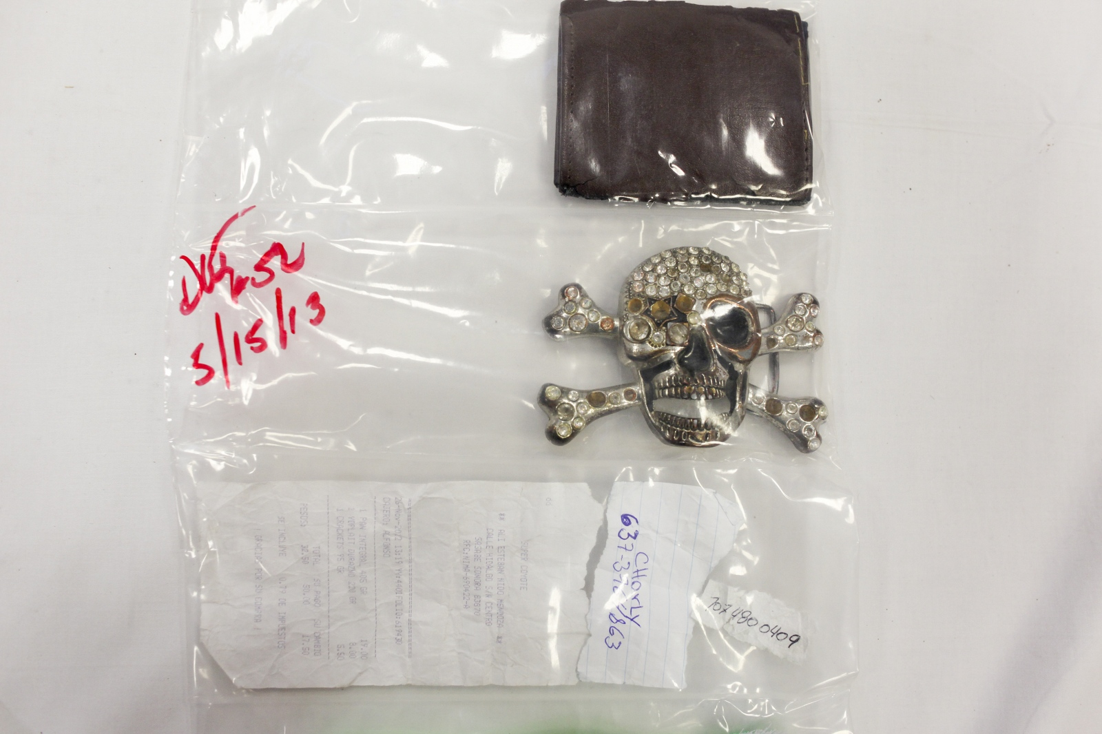 Belongings of an unidentified migrant border crosser are seen in a plastic sleeve displayed on a white sheet at the Pima County Office of the Medical Examiner on May 22, 2013, in Tucson, Ariz.  All remains, including the objects, are held for six to eight months and then cremated. The sheer volume of cases prevents the medical examiner from holding on any longer.  Each new item is carefully studied by Reineke and others from the medical examiner's office as they look for any clue to track down the families.