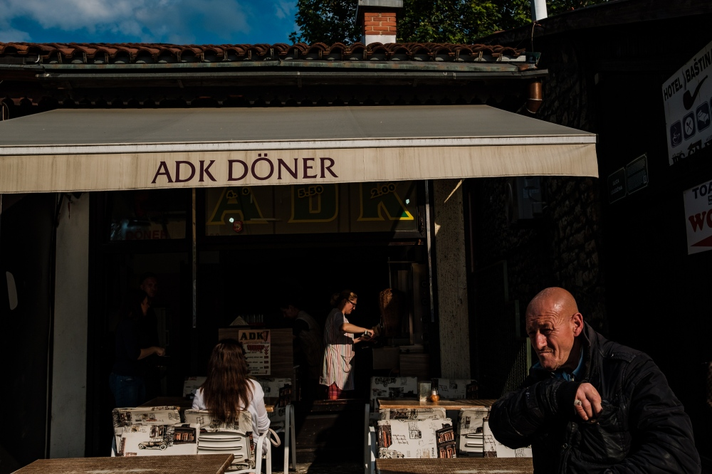 The owner and chef of this traditional Bosnian restaurant looks out onto the streets of the Old Town as evening sets in. This restaurant has been in the family for generations.