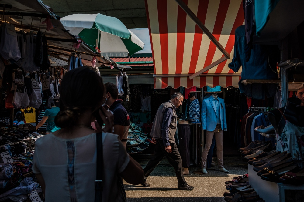 Locals walk through a day market set up near a freeway bridge outside the city center. Sarajevo remains at the crossroads between modernizing and tradition.