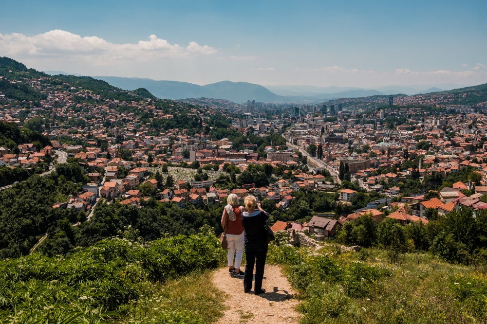 Two women take photos of the city of Sarajevo from an elevated vantage point. For more than four years from 1992 until 1996, shells and sniper fire rained down from these very hills onto the citizens of Sarajevo.