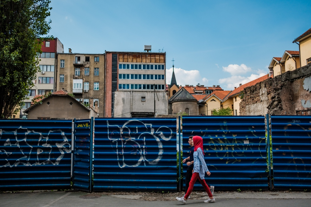 A Muslim girl and her friend walk near a graffiti-covered wall in downtown Sarajevo. The city continues to display a diverse mix of religions and ethnicities in spite of its troubled past.