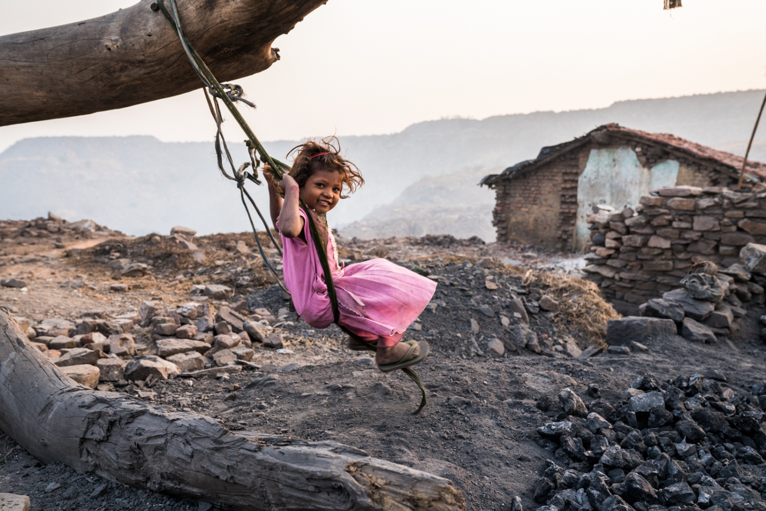 A girl swings on a dead tree. Her family's home is the last. It sits on the edge of a collapsed landscape.