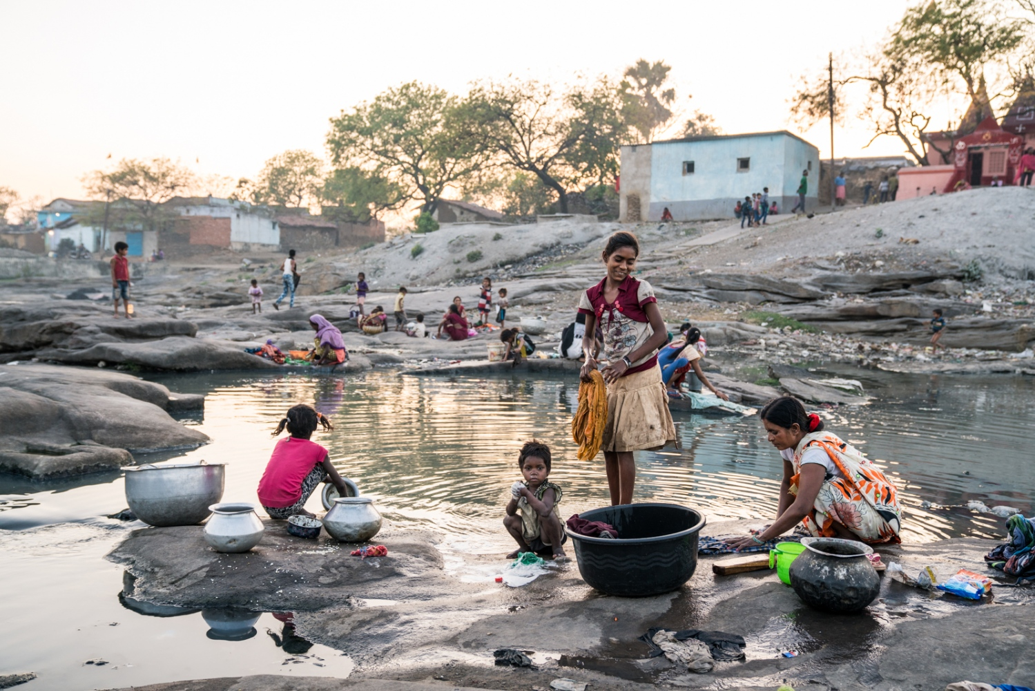 Women and children of Jharia wash dishes and clothing in the river that is polluted with mine tailing and sewage.