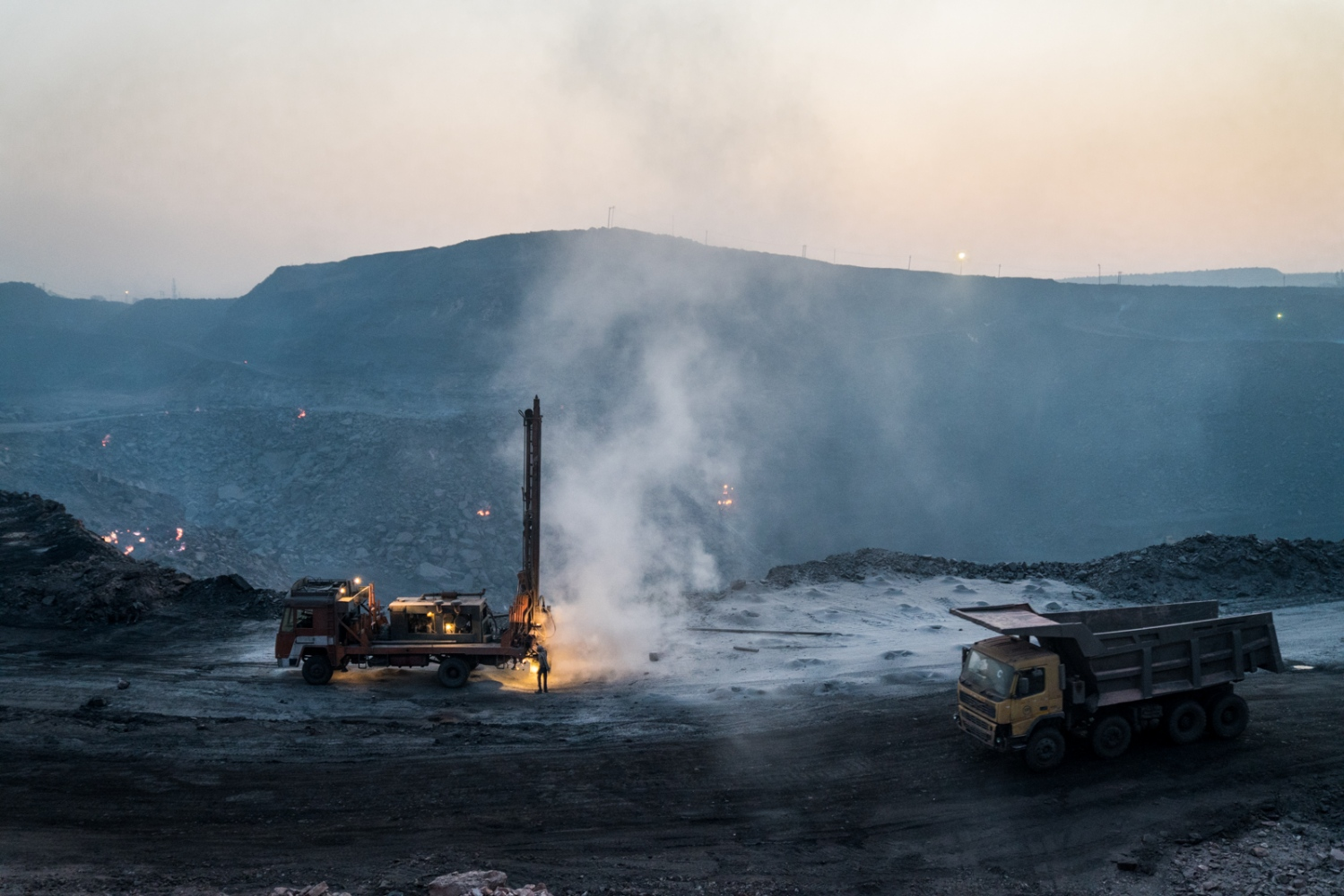 One of Jharia's largest opencast coal mines being worked on. Patches of red in the distance show the extent of the fire.