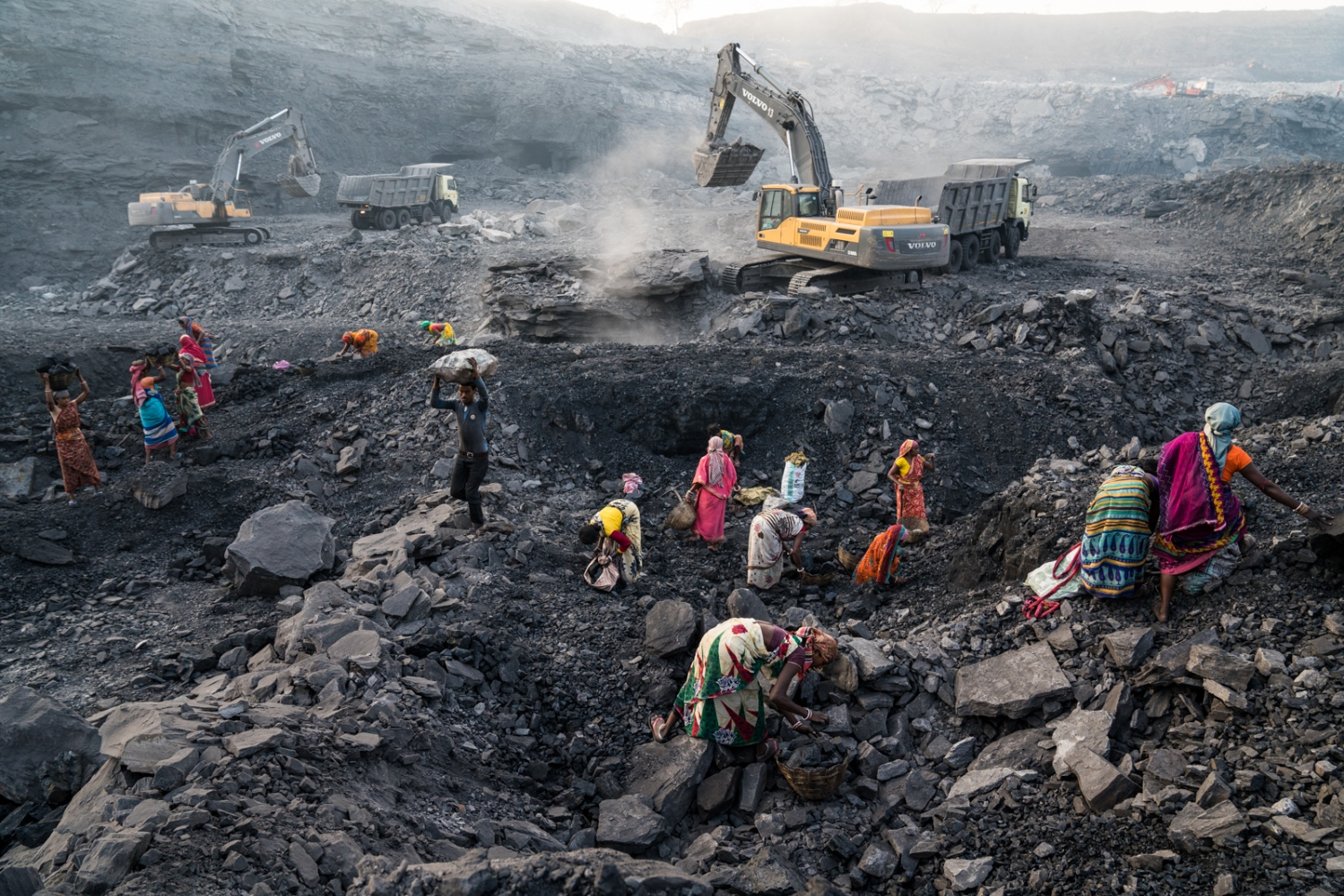 Women scavenge for coal to sell on the black market under extremely dangerous conditions working alongside heavy machinery.