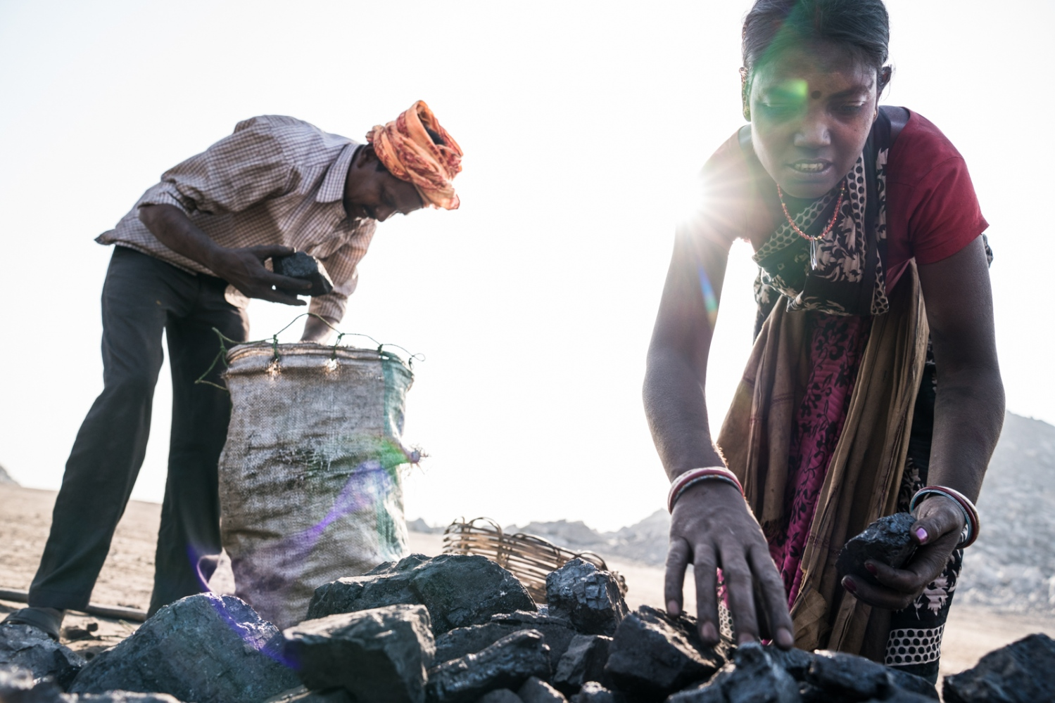 A women and man select the best coal pieces for transport to the black market after scavenging inside a coal mine.