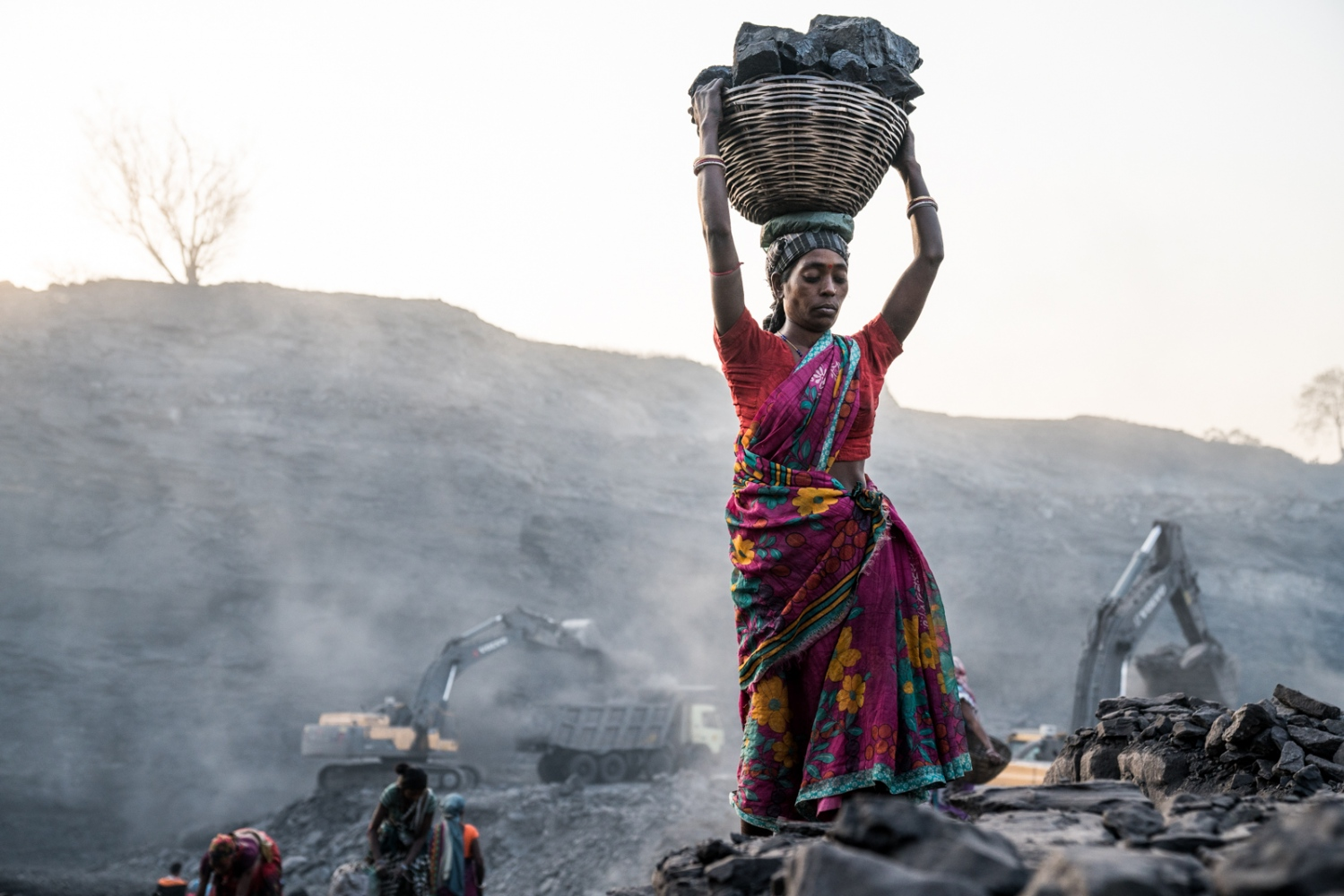 A woman scavenging coal carefully walks up the hill balancing a basket of coal on her head for sale on the black market.