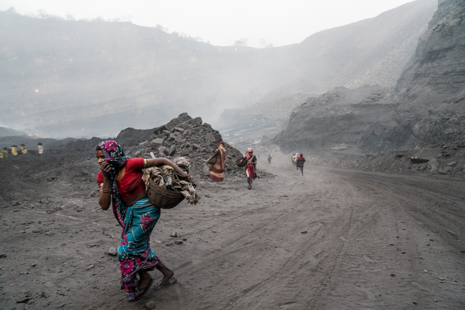 Women run with their belongings after hearing that the police are coming to the mine to check for scavenger activity.