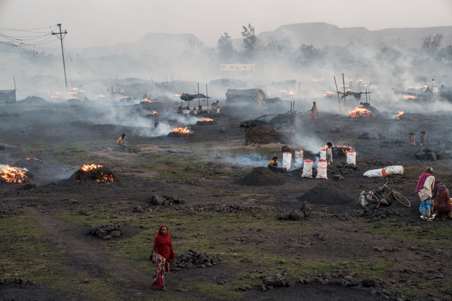 An area where scavenged coal is brought to be burnt and produce charcoal to be sold on the black market. A thick cloud of particulate and gaseous pollution blankets the area and contributes to and exacerbates already dangerous air quality.