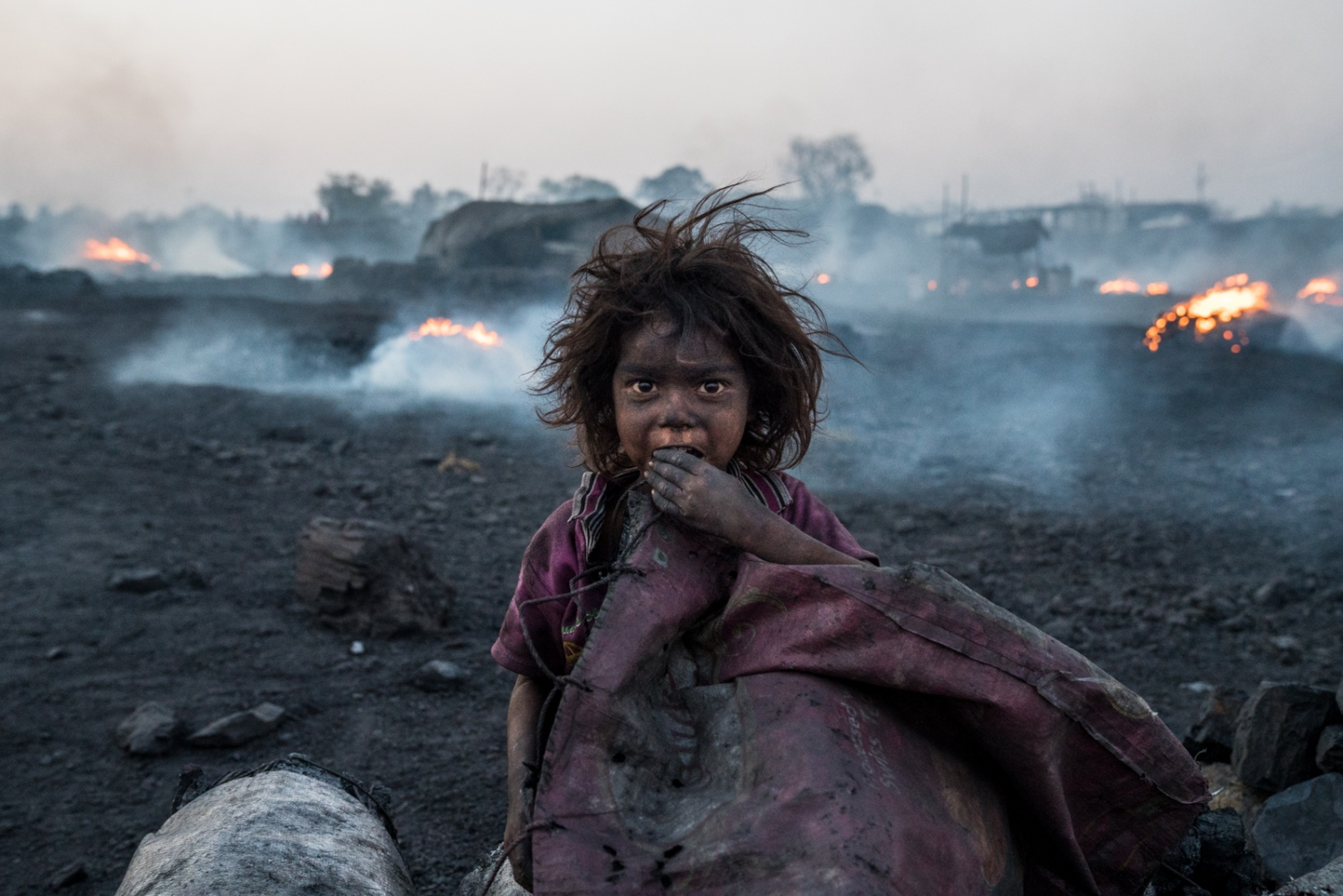 A child inside an area where scavenged coal is burnt to produce charcoal, which is sold on the black market. Many children are found in high-risk areas where their parents work to make a living.