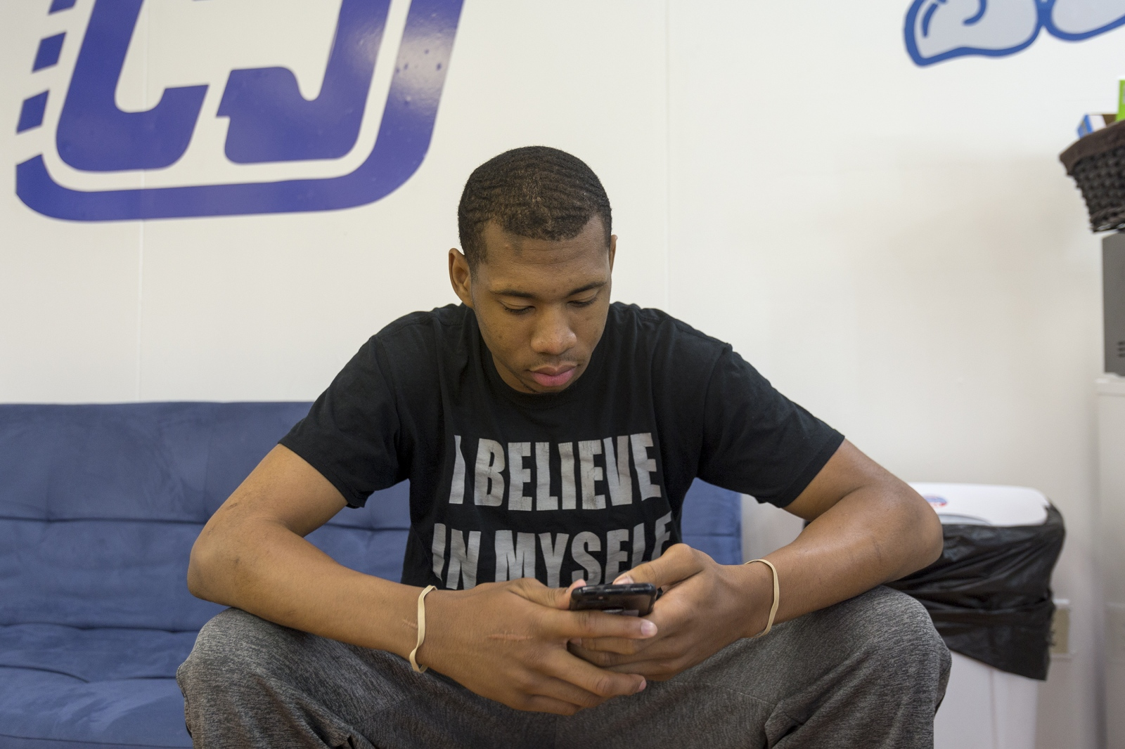 """I believe in myself,"" reads Michael Green's t-shirt as he checks his phone waiting for a haircut.  Michael is preparing for his senior prom, weeks before he graduates and then heads to college on a basketball scholarship."