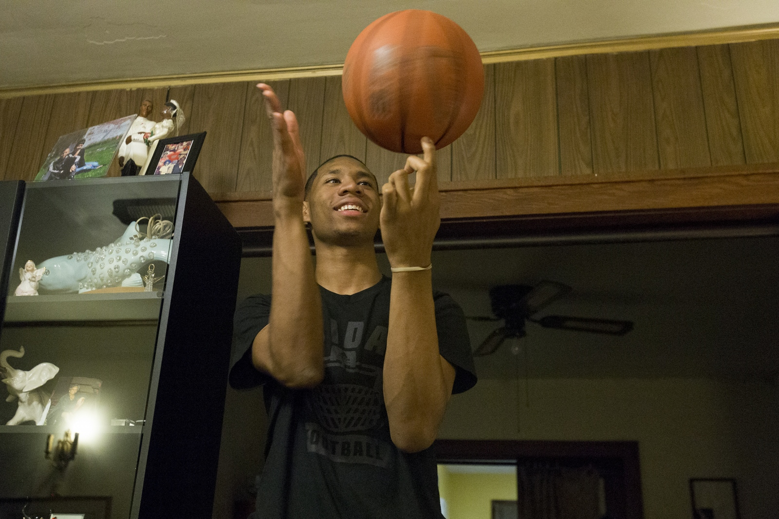 Michael spins a basketball on his finger late one evening in his living room.