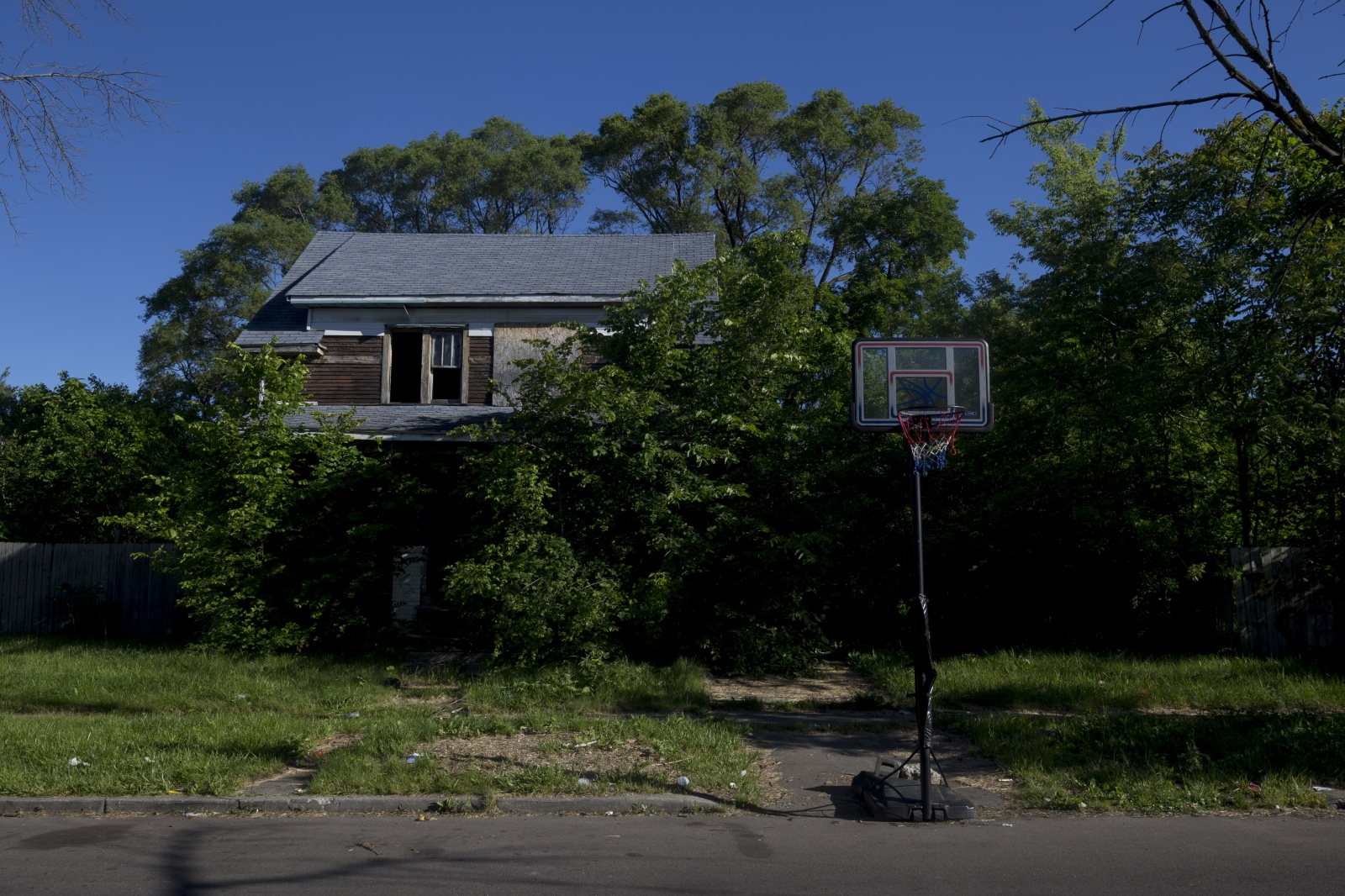The morning of Michael Green's high school graduation. Five years after being shot, the same basketball hoop stands down the street from Michael's home. Michael will attend Miles College in Alabama on a basketball scholarship.