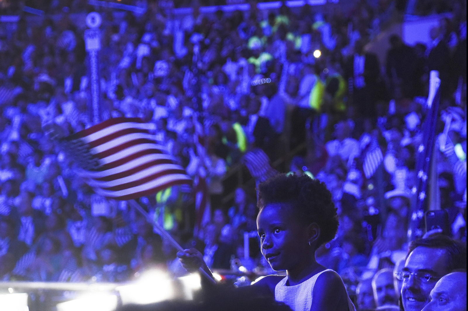 Philadelphia- A young girl is hoisted on the shoulders of her father as Michelle Obama takes the stage at the Democratic National Convention.