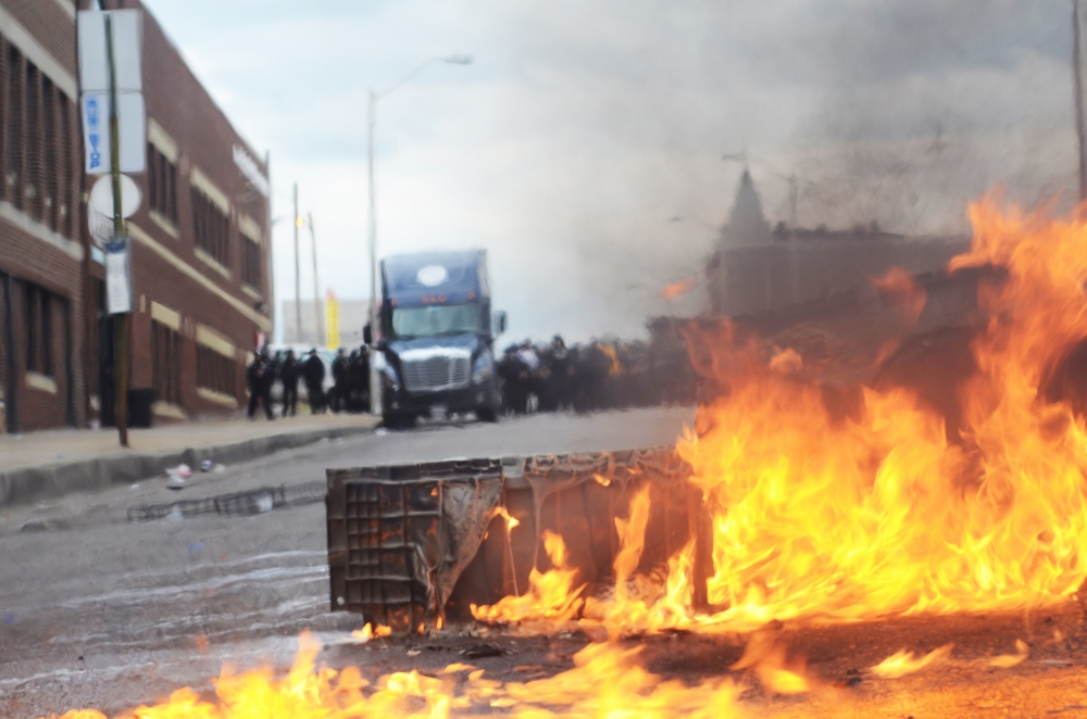 Baltimore-Police in the far background behind a flaming barricade during a riot in Baltimore.