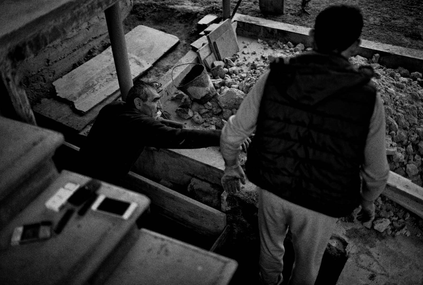 Two residents of Ashtarak, Armenia work to repair stairs leading to the basement of their home.