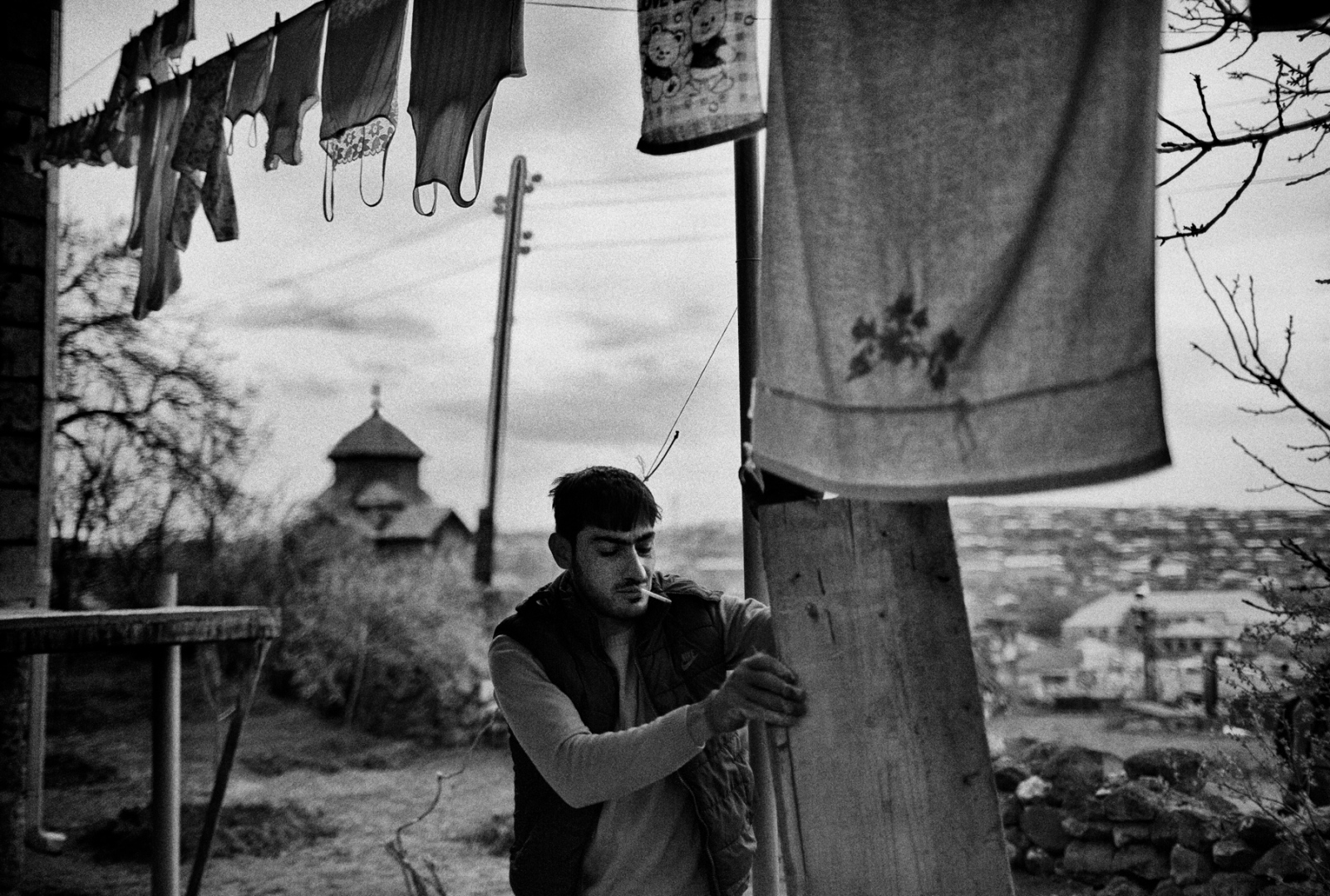 A resident of Ashtarak, Armenia works on some construction in his home. In the background the 7th Century Kamravor Church in may be observed.