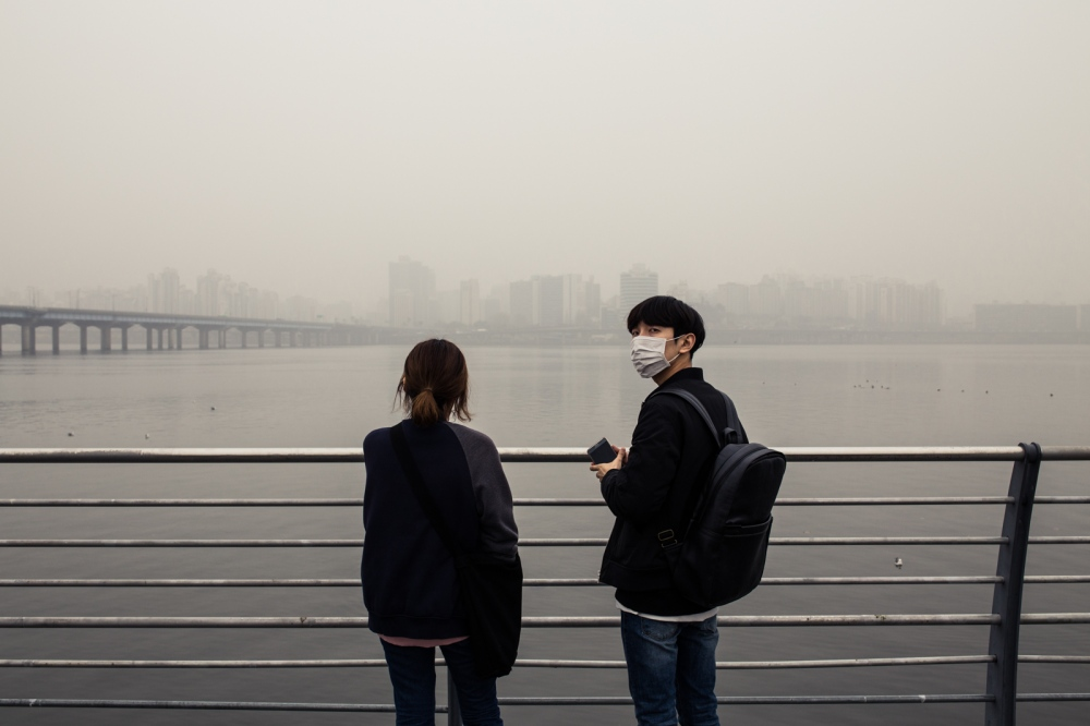 A couple on the Han River during a heavily polluted spring day. Seoul, South Korea.