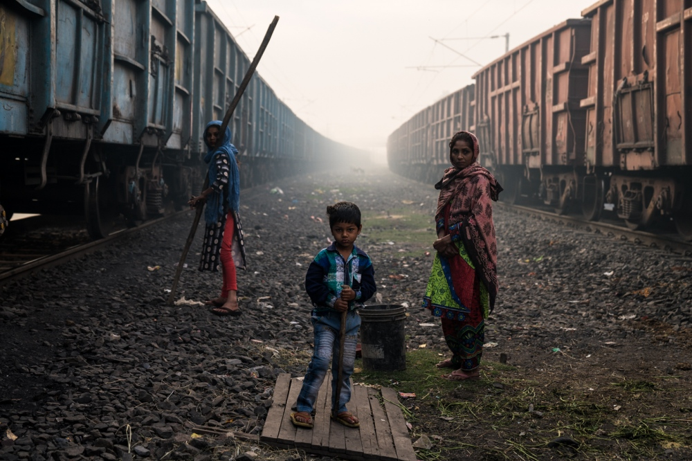 Family in-between two trains carrying coal. Central India.